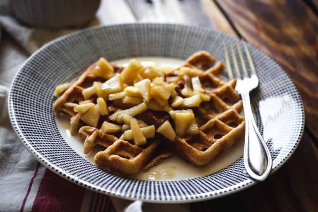 a plate of gluten free applesauce waffles with apple topping