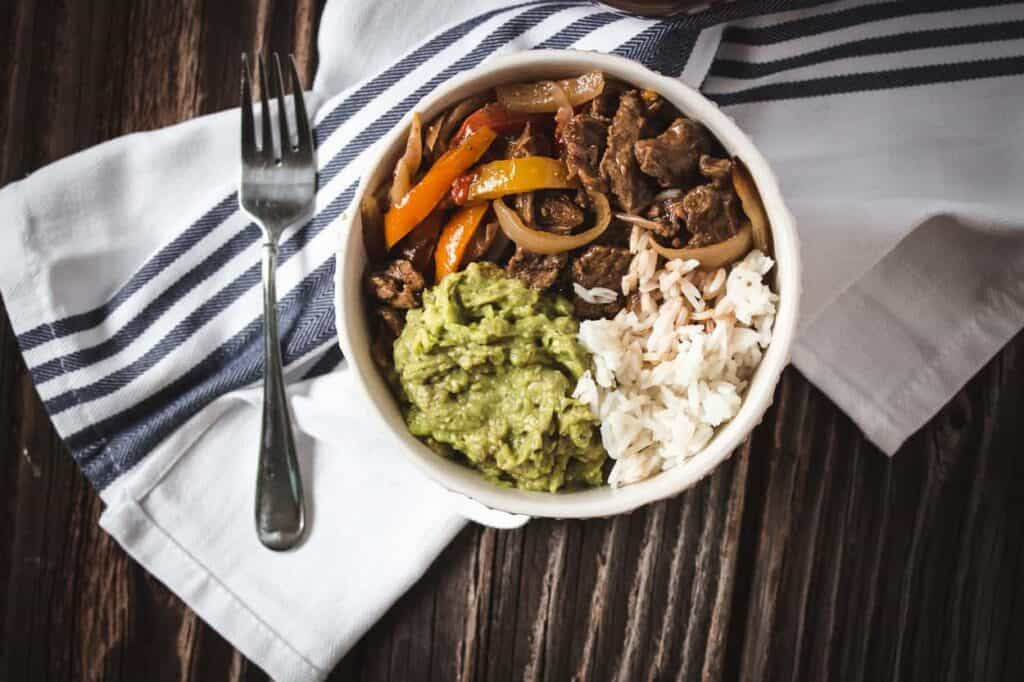 a white bowl of air fryer fajitas with jasmine rice and guacamole
