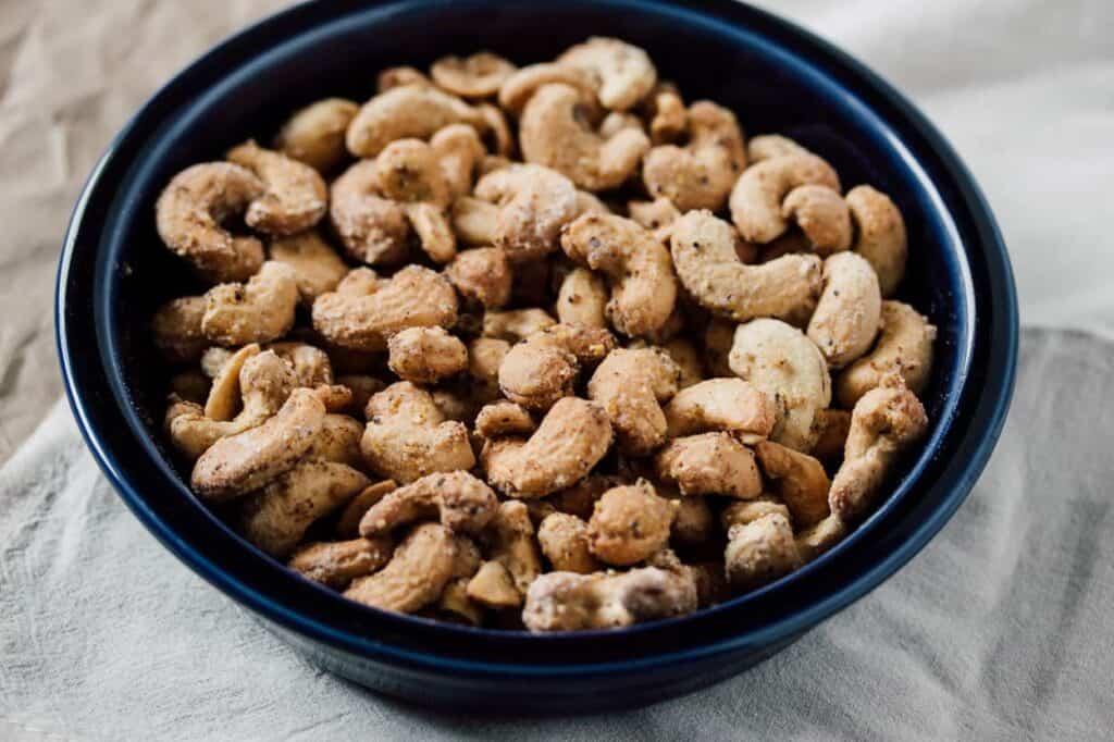 a dark blue fiesta ware bowl of air fryer salt and pepper cashews