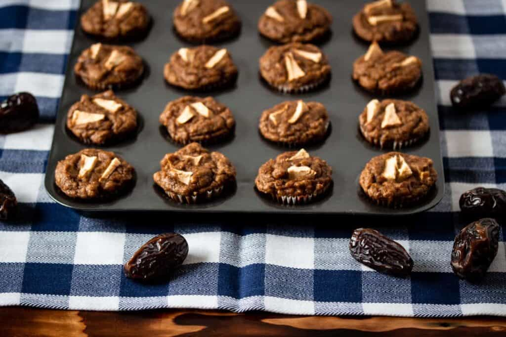 a baking pan with gluten free apple cinnamon mini muffins made with dates