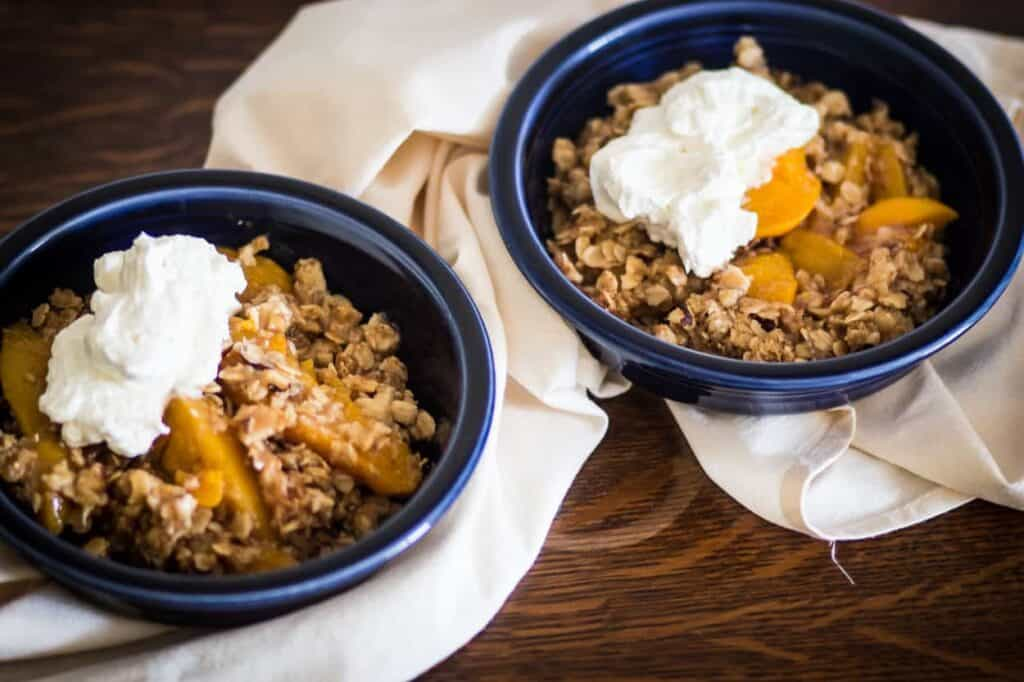 two bowls of gluten free peach cobbler with whipped cream