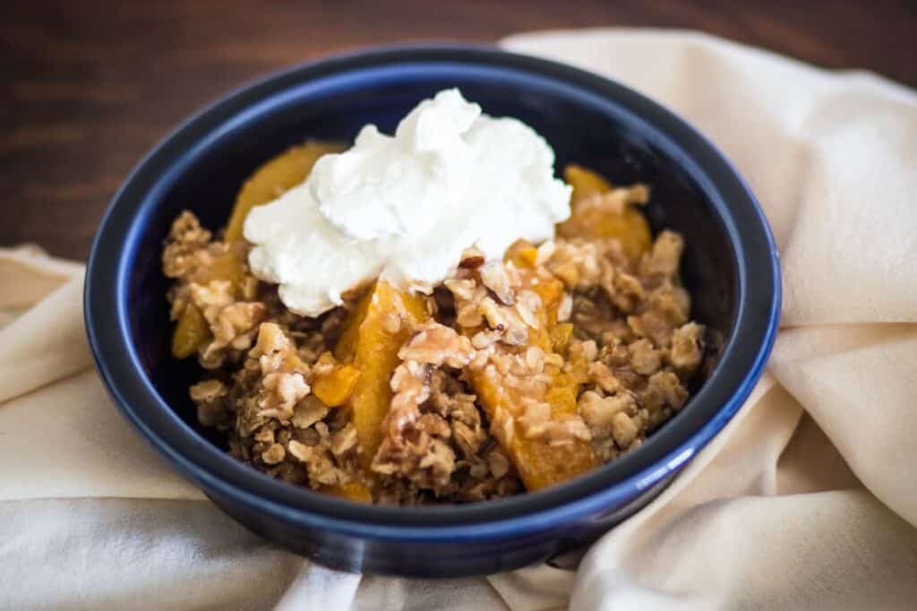a bowl of gluten free peach cobbler with a dollop of whipped cream