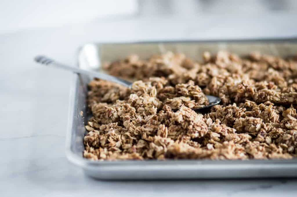 gluten free salty & sweet granola on a baking sheet with a spoon