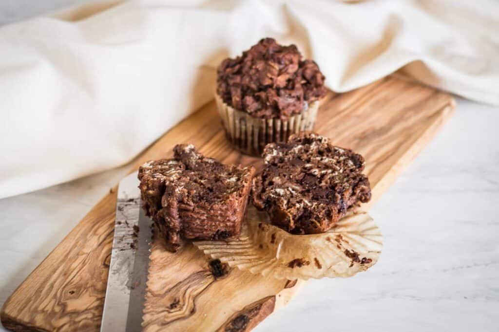 gluten free chocolate chip muffin cut in half on a cutting board