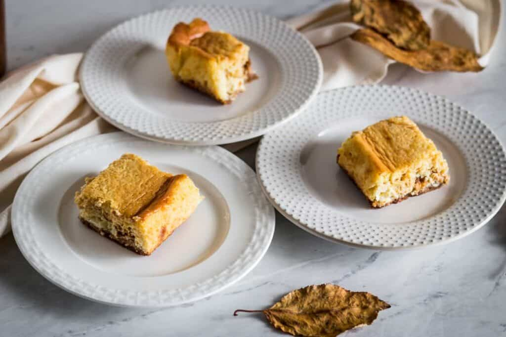close up of pumpkin cheesecake bars on plates