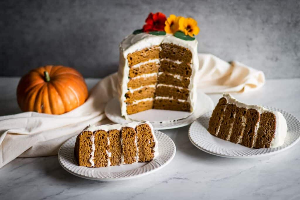 a gluten free pumpkin cake with cream cheese frosting next to two plates with slices of cake on them