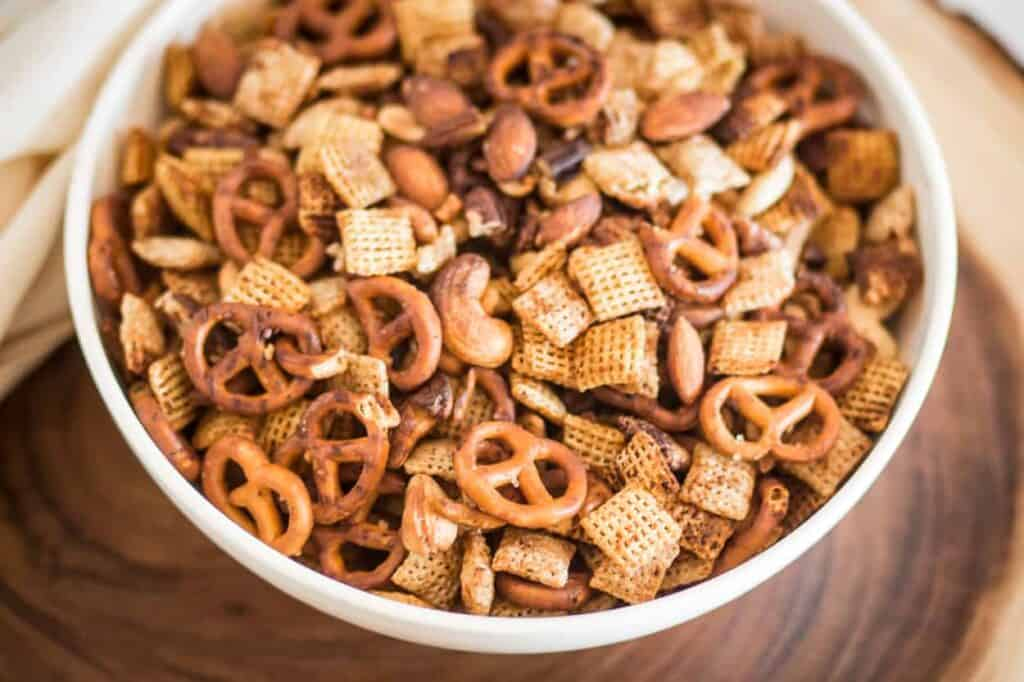 a white bowl of gluten free air fryer chex mix sitting on a round wooden board