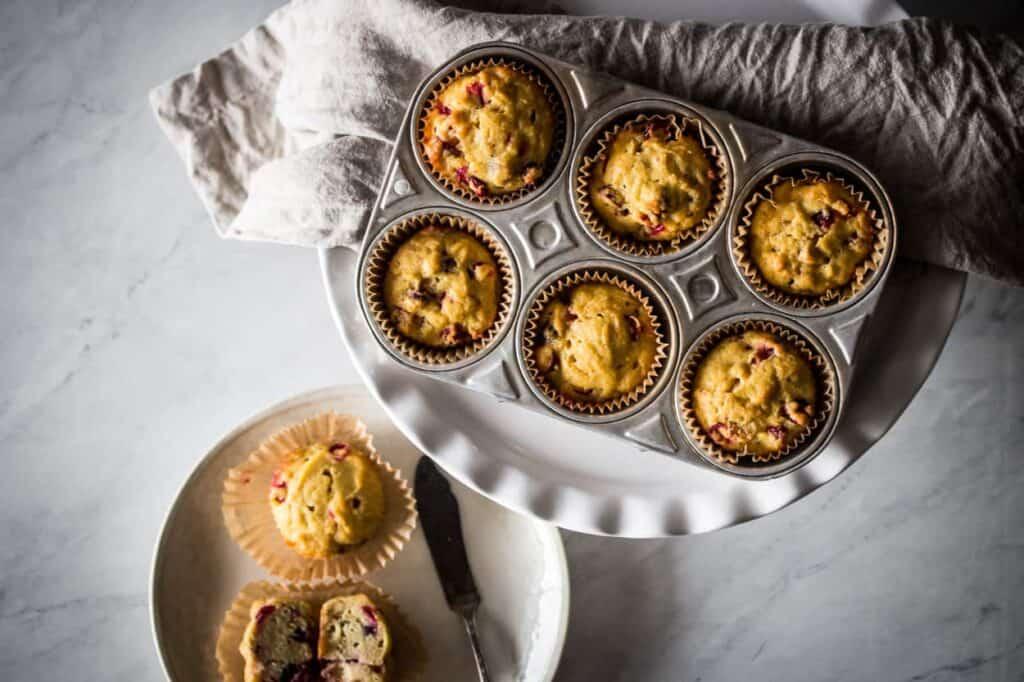 a muffin tin with six gluten free cranberry orange muffins