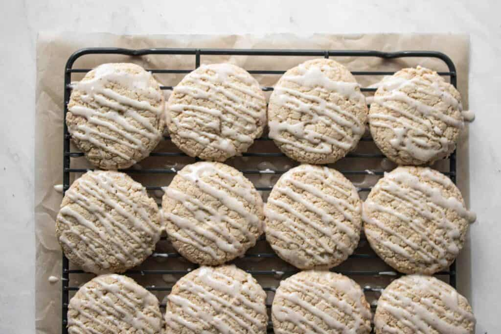 a cooling rack of gluten free eggnog cookies with a vanilla glaze drizzled over them