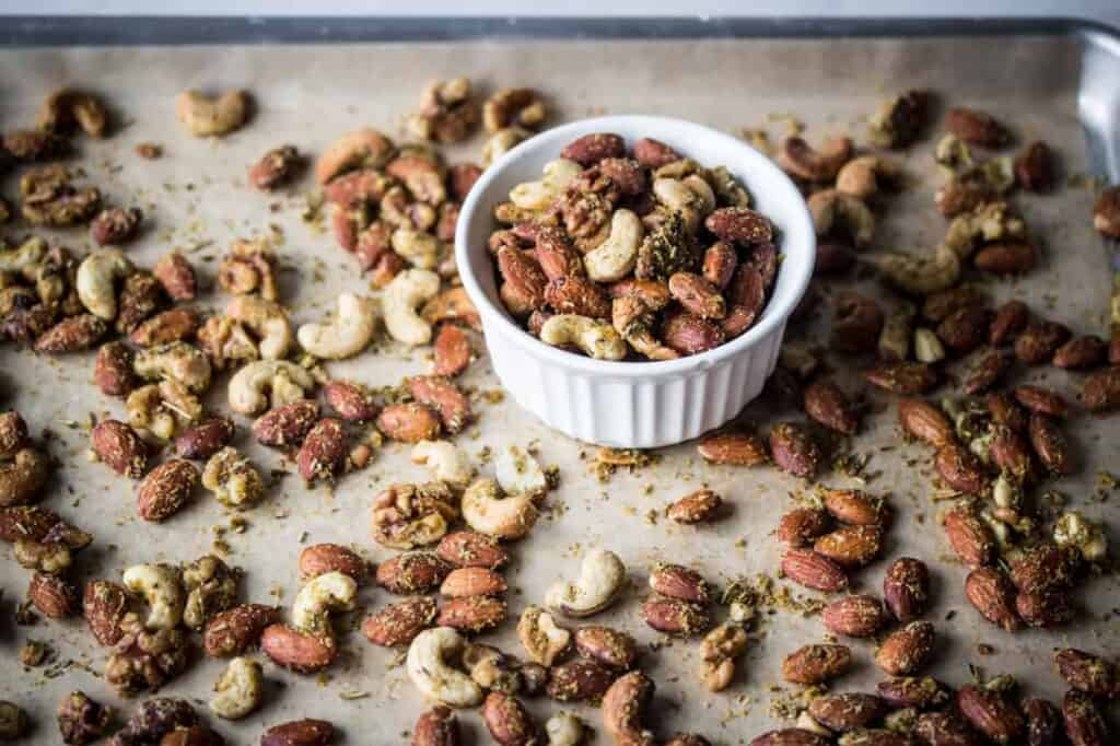 a baking sheet and small white bowl with air fryer savory herb roasted nuts