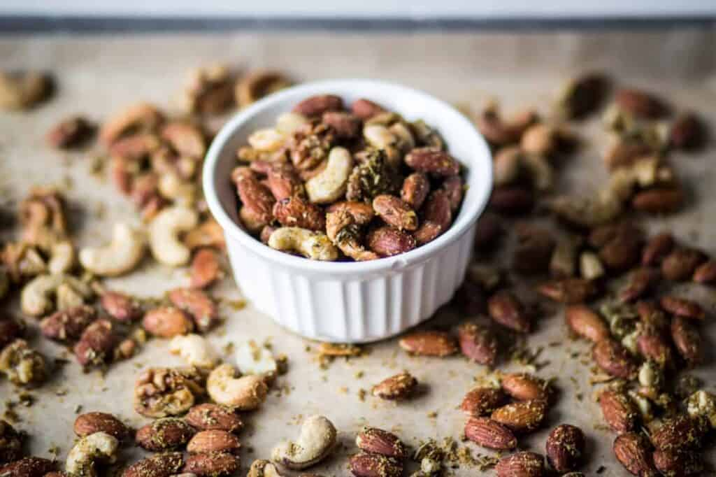 a small white bowl of air fryer savory herb roasted nuts sitting in the middle of a baking sheet of the nuts
