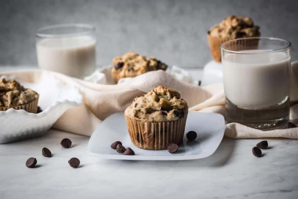 gluten free chocolate chip banana muffins on plates with two glasses of milk