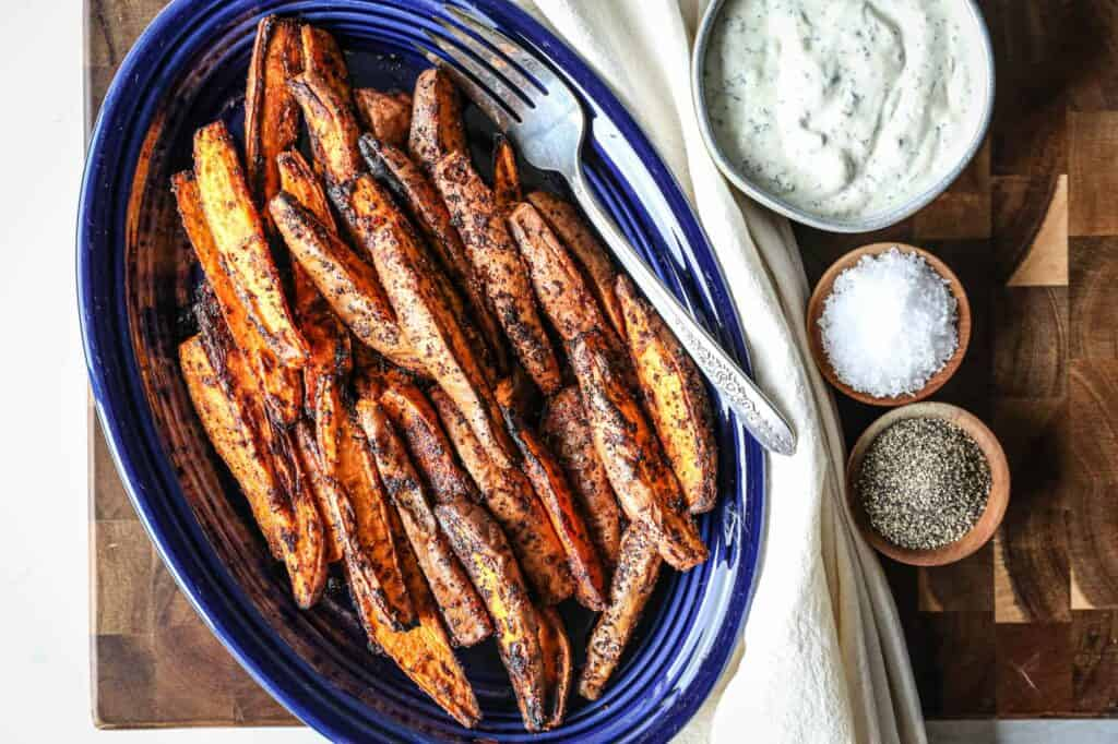 a plate full of gluten free air fryer sweet potato wedges with gluten free homemade ranch dip