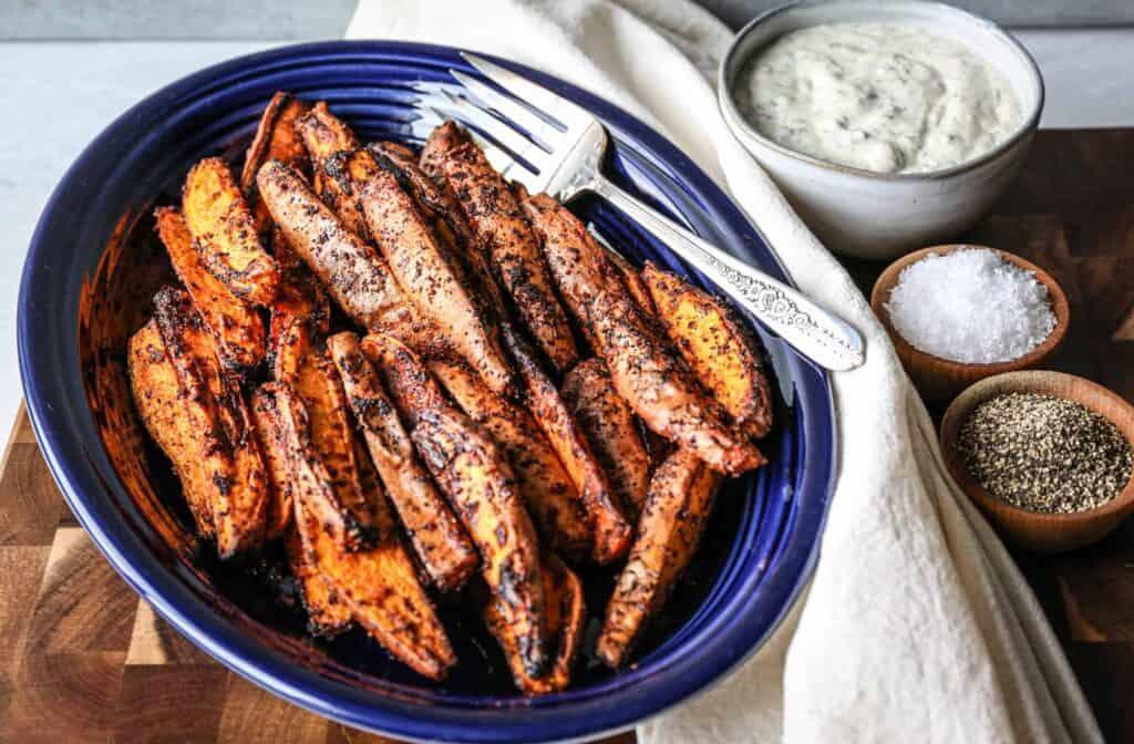 a blue fiesta ware platter of air fryer sweet potato wedges with a bowl of gluten free ranch dressing