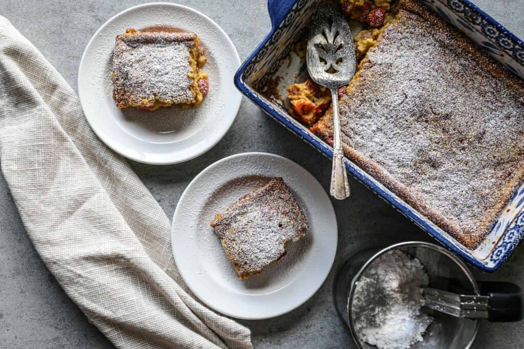 a 9-inch baking dish and two plates of gluten free sour cherry clafoutis sprinkled with powdered sugar