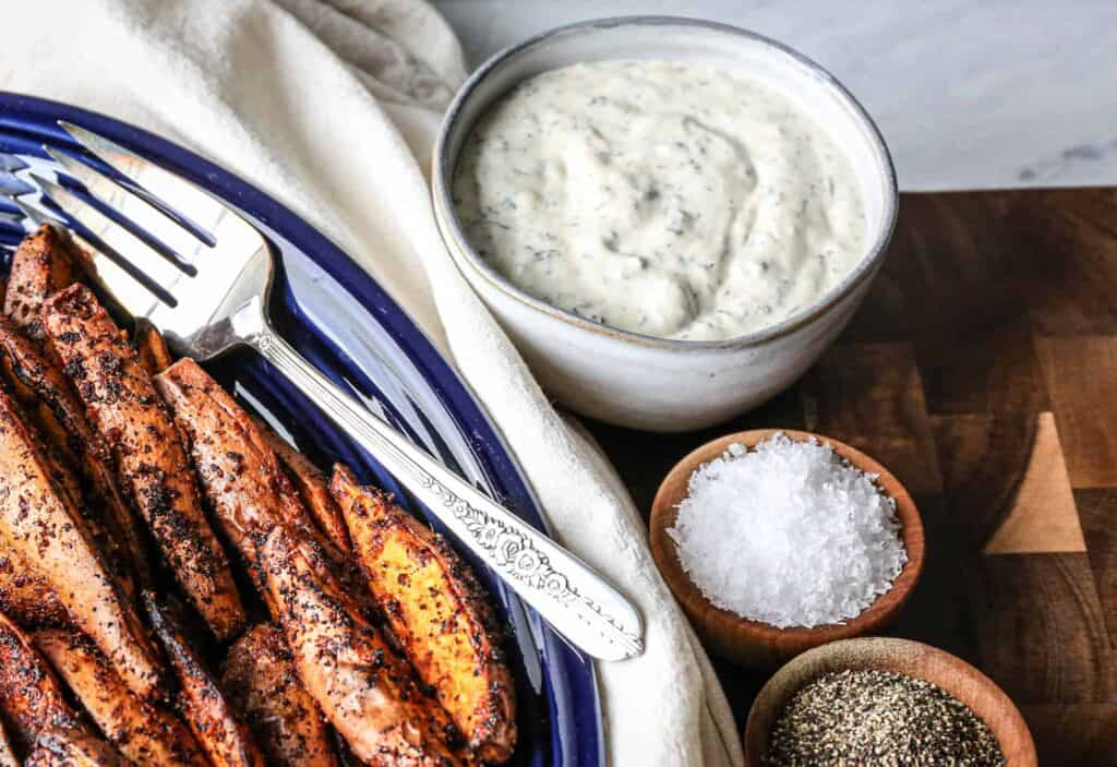 a small bowl of gluten free homemade ranch dip with air fryer sweet potato wedges