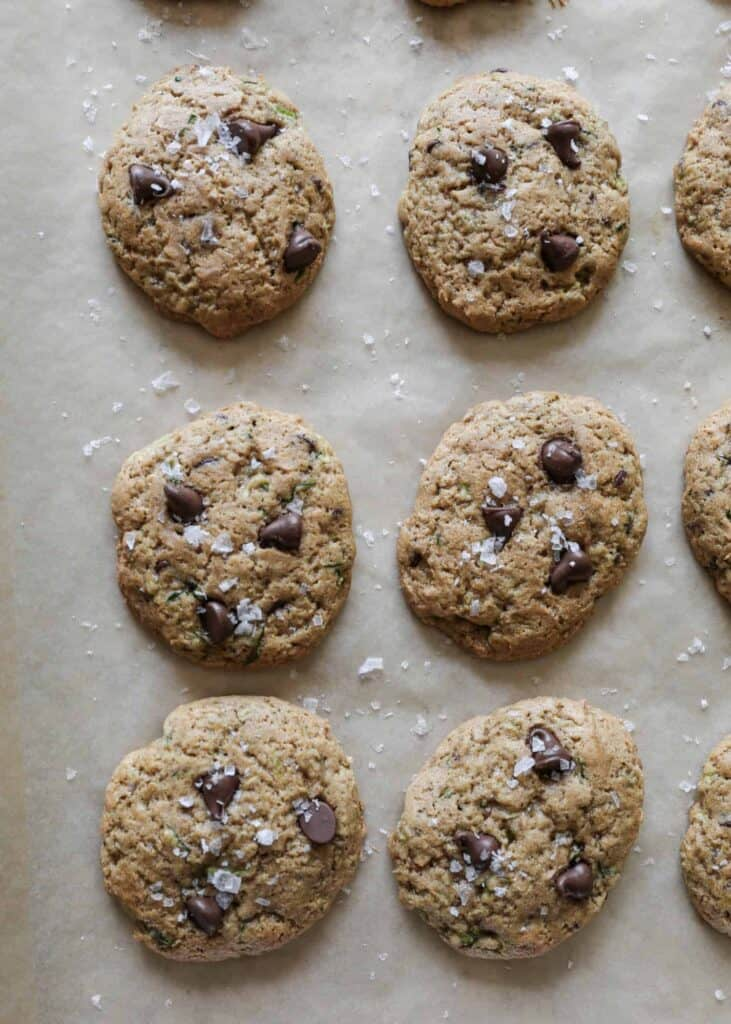 a close up of six gluten free zucchini chocolate chip cookies on a baking sheet