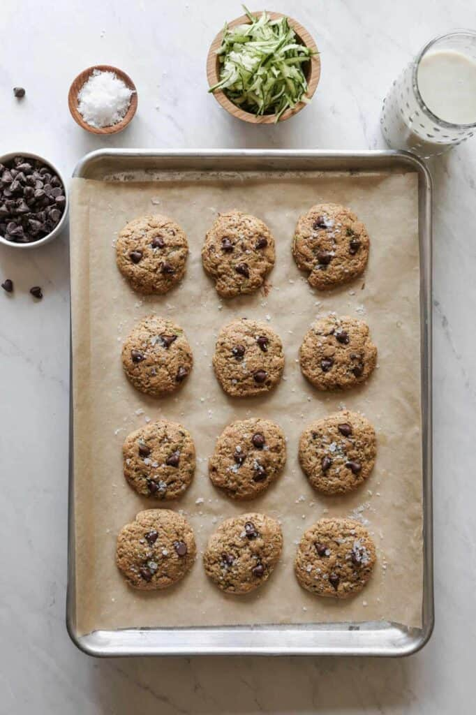 a baking sheet with twelve gluten free  zucchini chocolate chip cookies