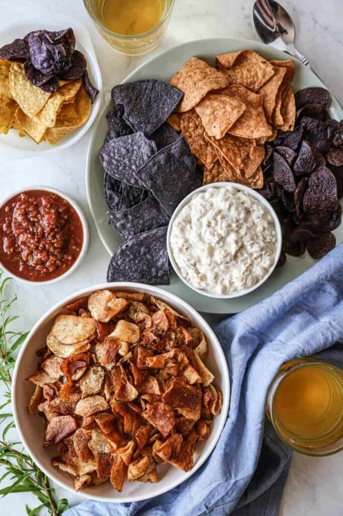 a bowl of caramelized onion dip surround by bowls of various types of chips that are perfect for your gluten free new years party snacks