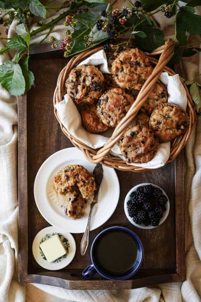 a basket of gluten free blackberry oat muffins on a tray with coffee, butter and blackberries