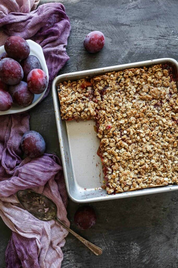 a nine inch baking pan with gluten free plum cake with a bowl of fresh plums