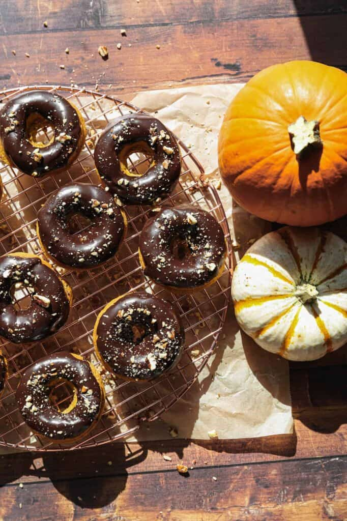 a cooling rack of gluten free baked pumpkin donuts with chocolate glaze sprinkled with chopped pecans
