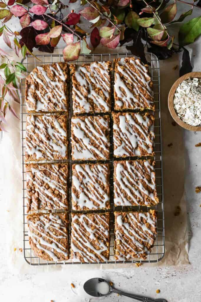 a gluten free pumpkin oatmeal cake cut into slices on a cooling rack with vanilla glaze drizzled over the top