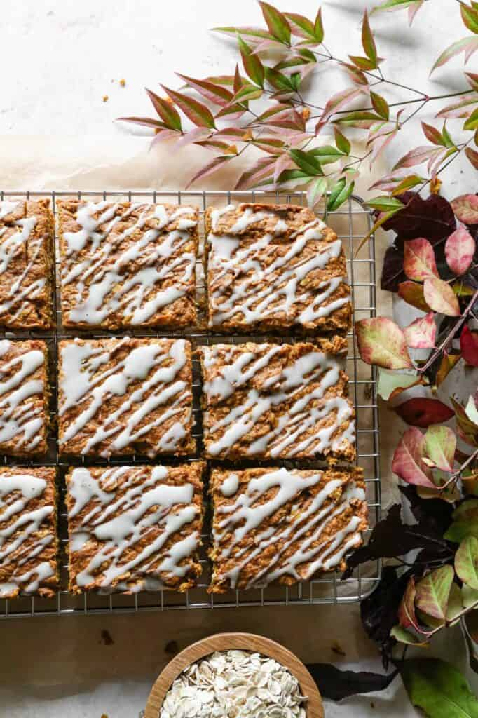 squares of gluten free pumpkin oatmeal cake on a cooling rack and drizzled with vanilla glaze