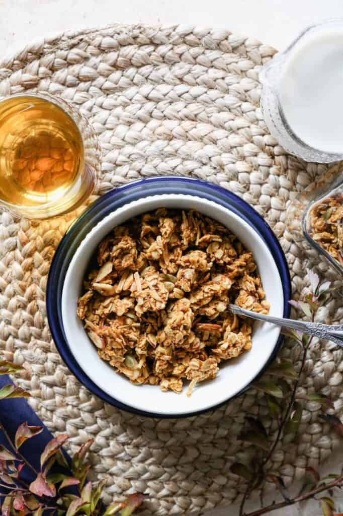 a bowl of gluten free pumpkin pie granola with a glass of apple juice and a pitcher of milk