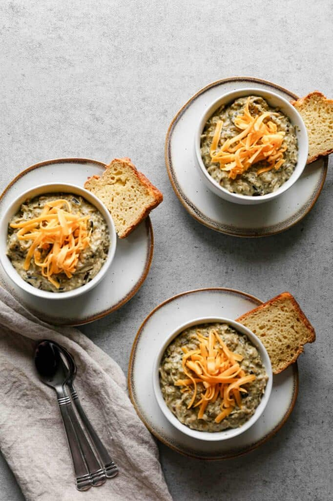 three bowls of gluten free instant pot chicken and broccoli casserole with shredded cheddar cheese and gluten free sourdough bread