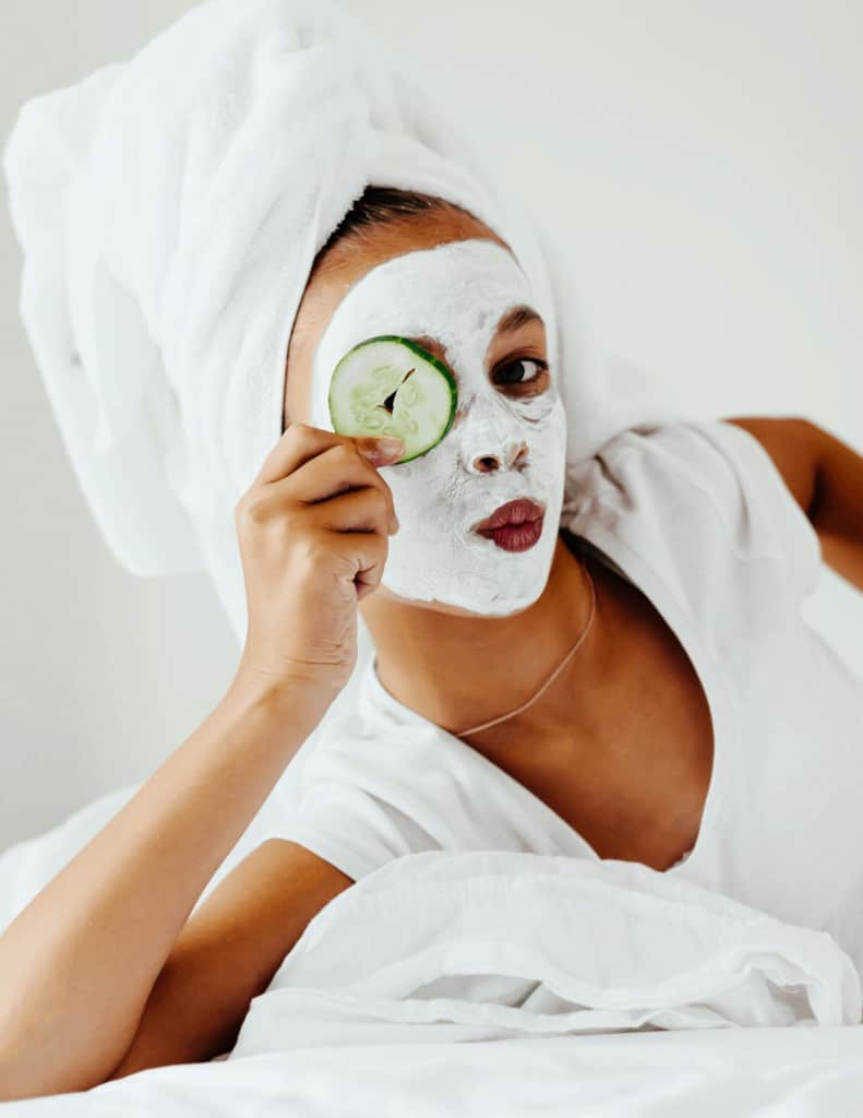 a woman having the perfect at home facial with a face mask on holding a cucumber slice over one eye.