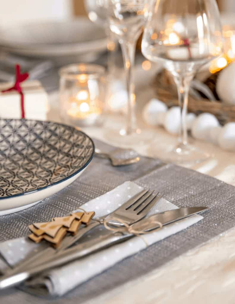 a Christmas table setting with plate, wine glasses, silverware and candles