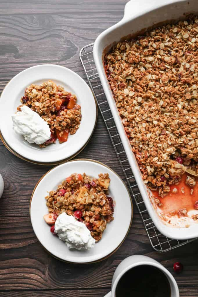 a baking dish with two plates of gluten free cranberry apple crisp served with fresh whipped cream