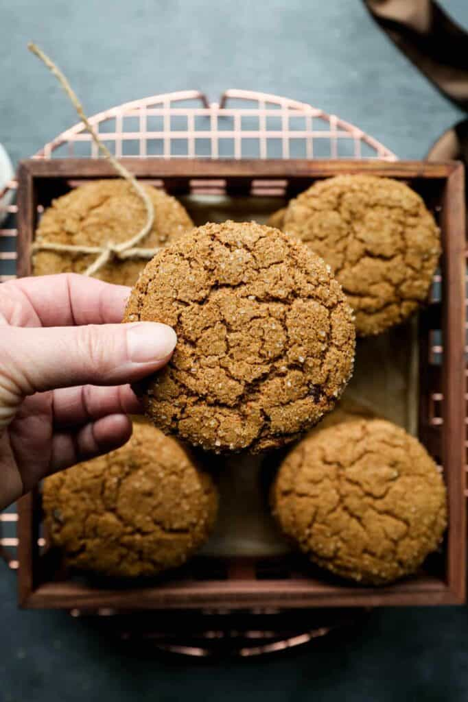 a box full of gluten free ginger cookies with me holding one in my hand