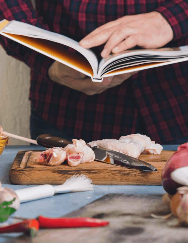 a person using a cookbook while cooking in their kitchen