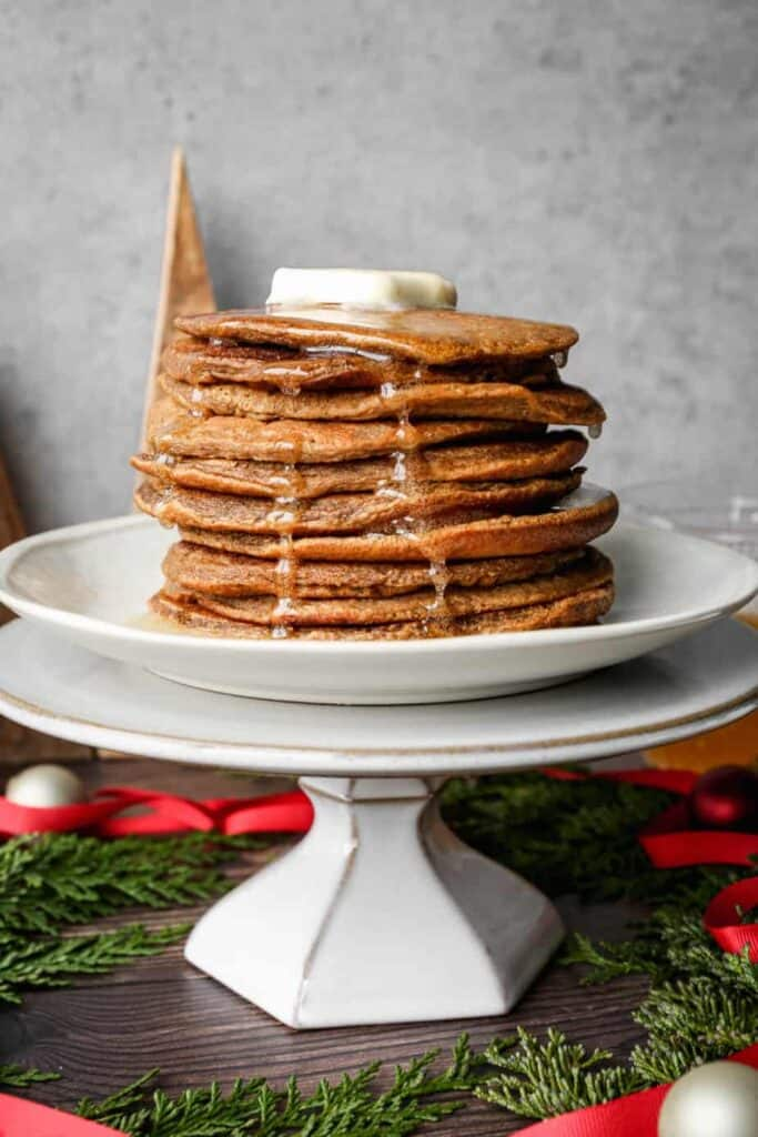 a stack of gluten free gingerbread pancakes with ginger syrup poured over them
