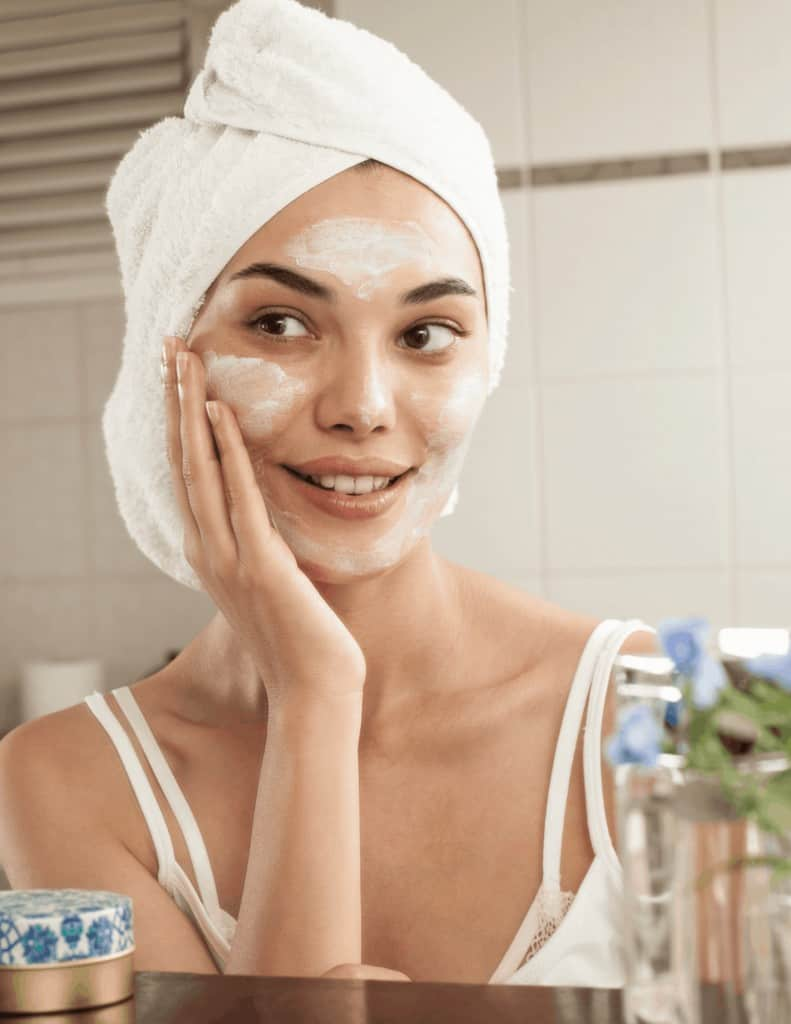 a woman with a towel on her head rubbing cleanser onto her face