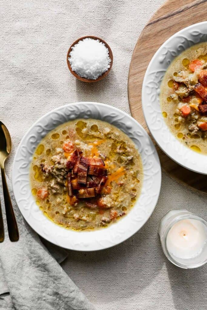 two white bowls of gluten free instant pot cauliflower cheeseburger soup with a small bowl of salt and two gold spoons