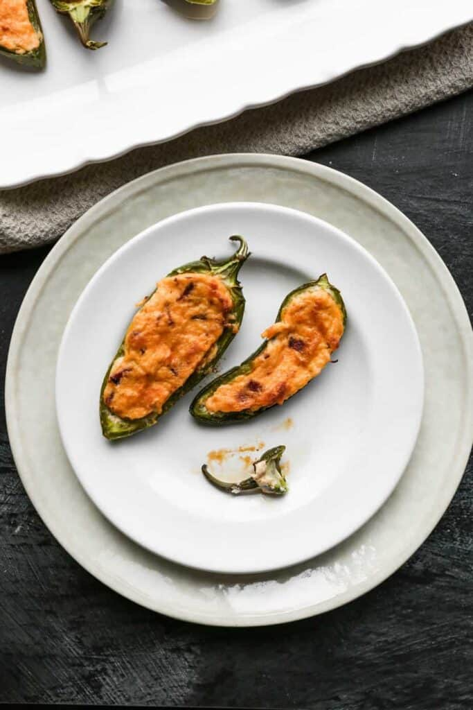 a white plate of baked gluten free jalapeño poppers