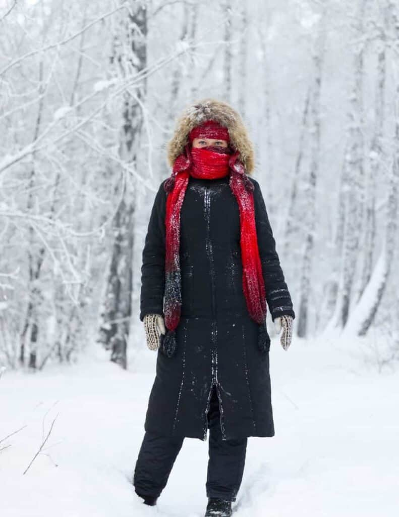 a woman in the snow bundled up in a jacket, hat and scarf