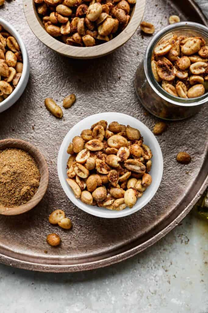 small bowls of air fryer spicy roasted peanuts on a large copper tray