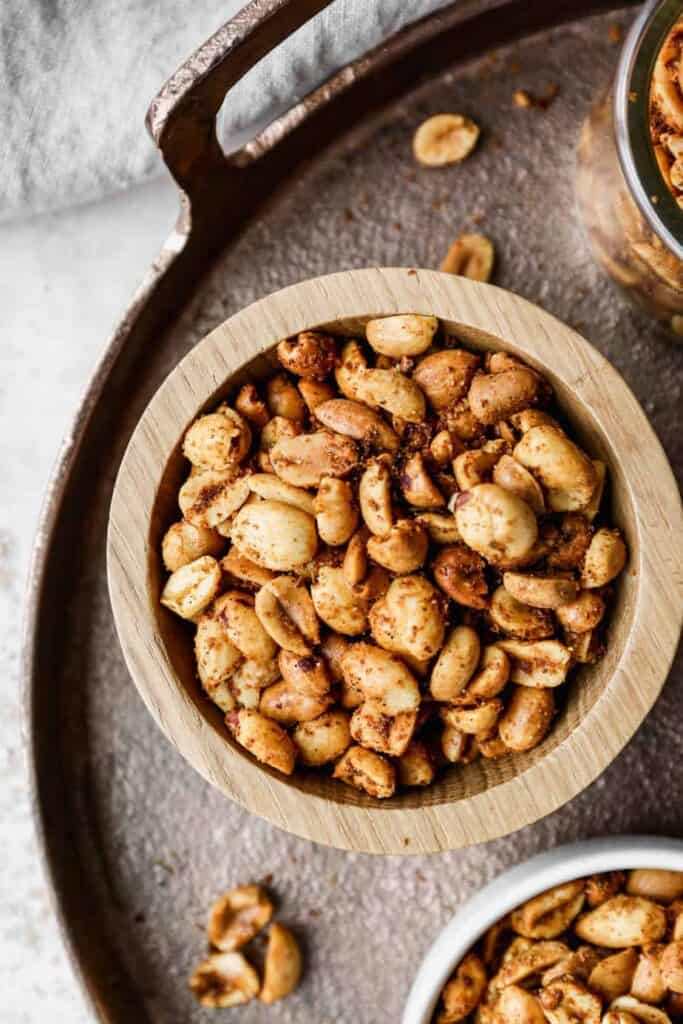 a small wooden bowl of air fryer spicy roasted peanuts on a copper tray