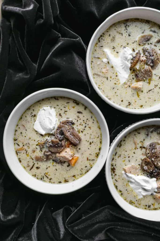 three white bowls of gluten free instant pot chicken and mushroom soup with a dollop of sour cream on top