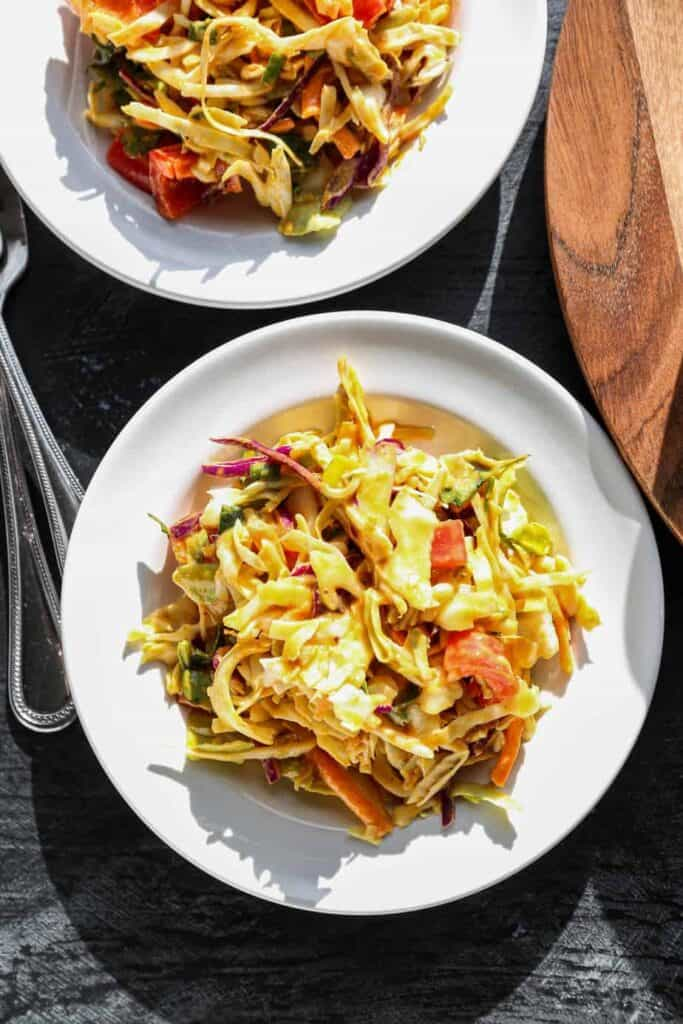 two white salad plates with thai style cabbage salad with a peanut dressing