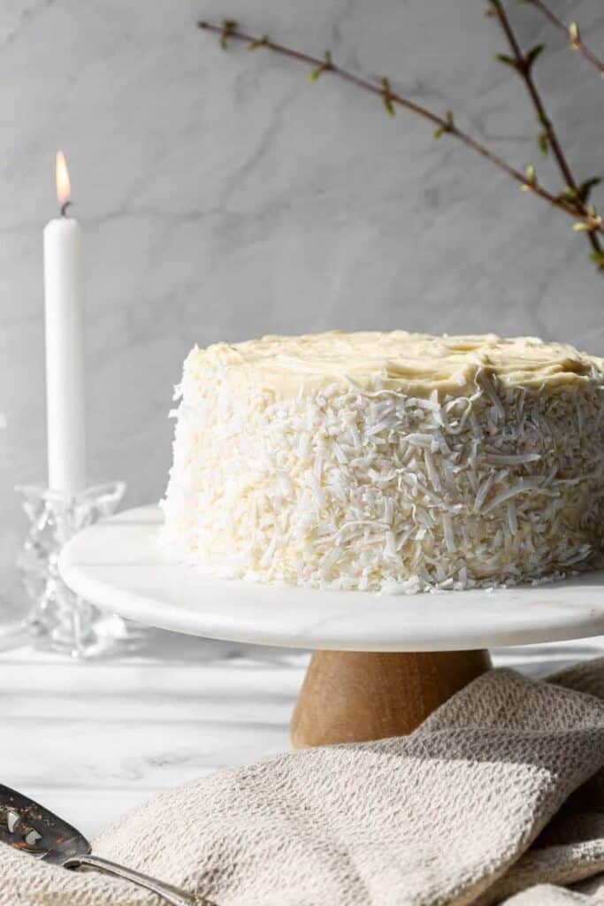 a gluten free coconut cake with white chocolate buttercream frosting and sweetened coconut flakes pressed on the sides. The cake is on a marble and wood cake stand.