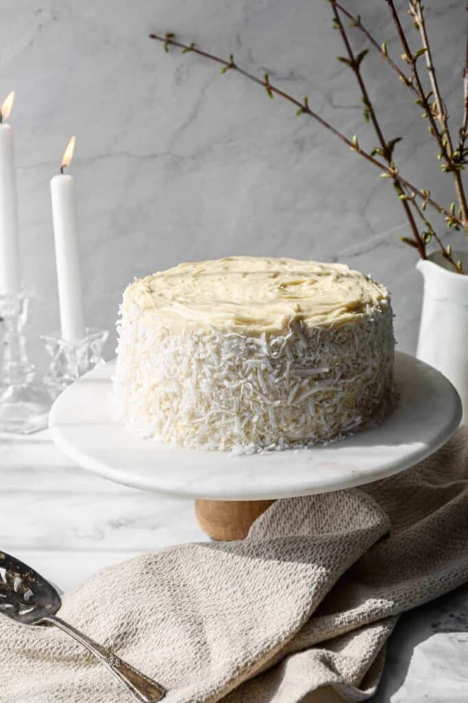 a gluten free coconut cake frosted with white chocolate buttercream frosting on a marble and wood cake stand