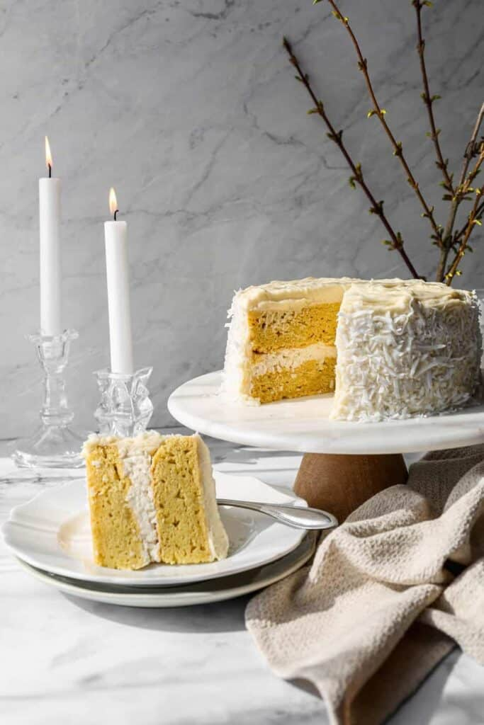 a gluten free coconut cake with white chocolate buttercream frosting and coconut flakes around the sides on a marble and wood cake stand