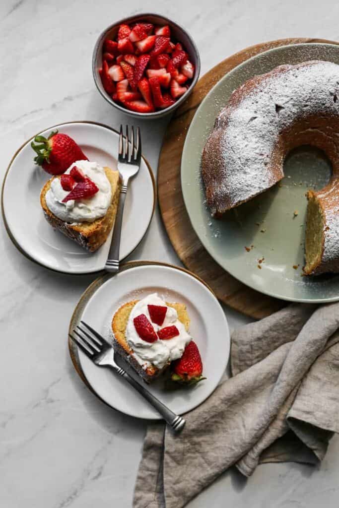 a gluten free cream cheese pound cake on a light blue platter with two slices on white plates with sliced strawberries and homemade whipped cream