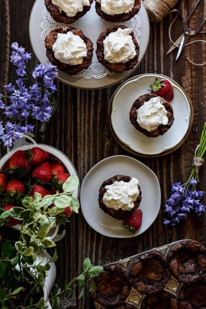 gluten free brownie bites on a white plate and a white cake stand with homemade whipped cream on top and fresh strawberries