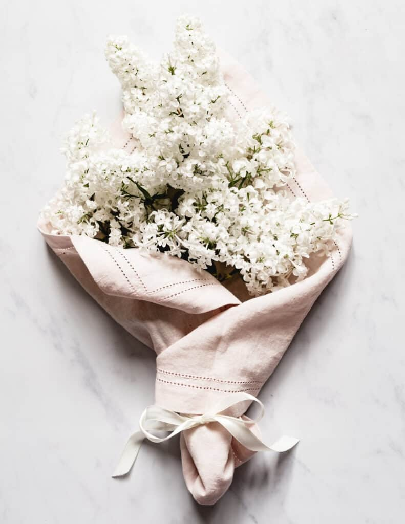 a marble background with one of my favorite things, white lilac blooms wrapped in a light pink linen napkin and tide with white ribbon